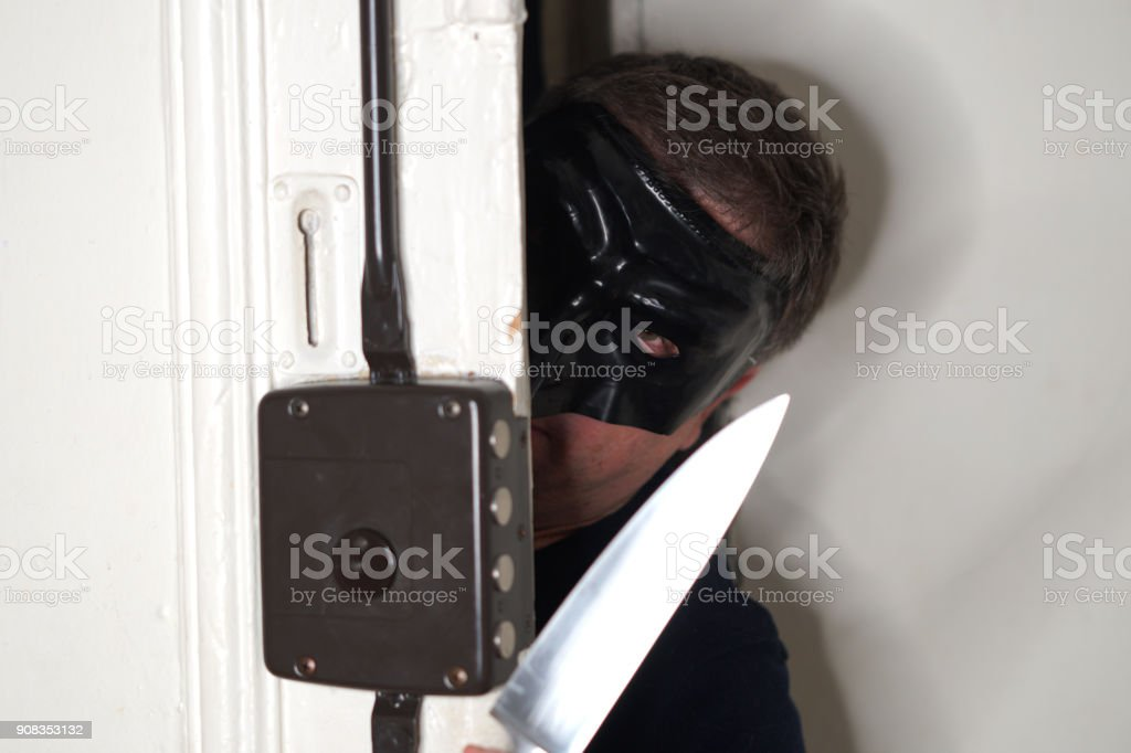 Masked housebreaker armed with a dagger opening a door stock photo
