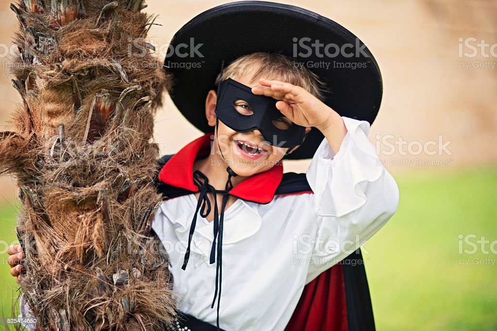 Masked little boy hero sneaking behind palm trees stock photo
