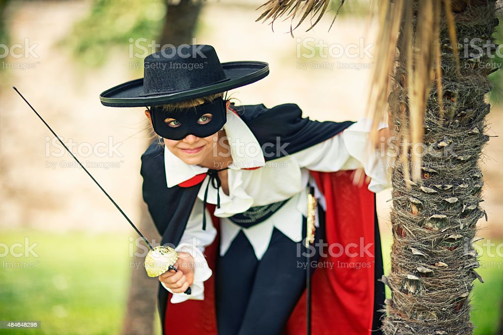 Masked little girl hero sneaking behind palm trees stock photo