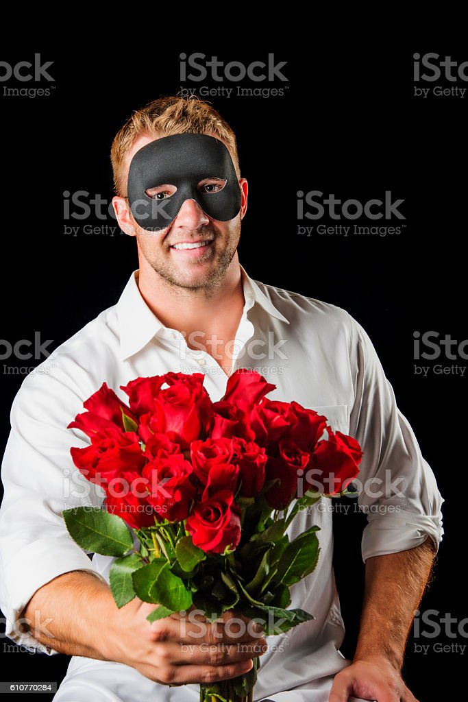 Masked Man Holding a Dozen Roses stock photo