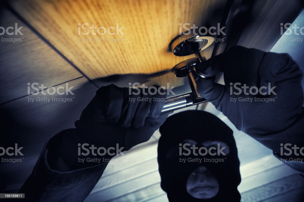 Masked man opening the door stock photo