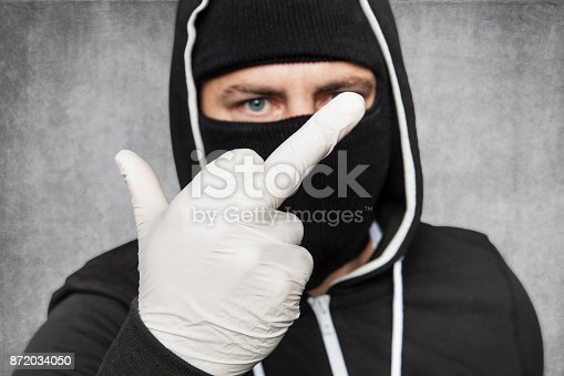 istock masked man shows middle finger 872034050