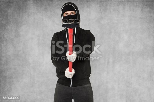 istock masked man with big hammer 872033900