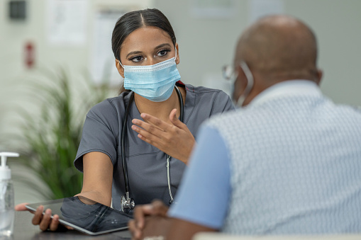 A senior patient and a female doctor meet in a medical clinic while wearing protective face masks to avoid the transfer of germs.