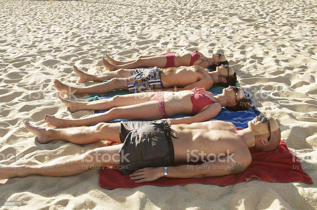 masked people on the beach sunbathing foto stock royalty-free