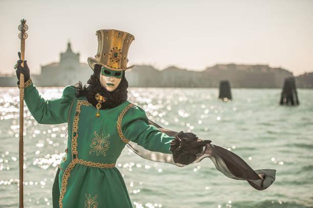 Maskierte Person in grünen Karneval Kostüm mit goldenen Hut posiert in der Nähe von Canale Grande, Venedig – Foto