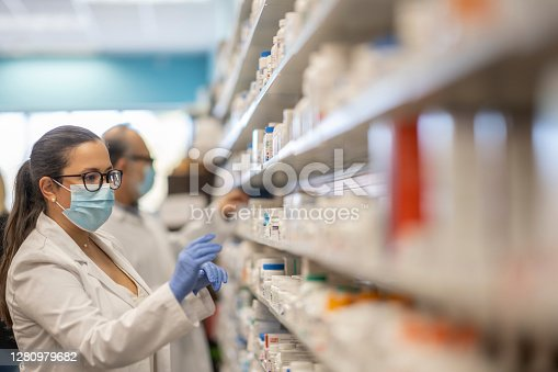 Pharmacist working at a pharmacy organizing products while wearing a protective face mask during the coronavirus outbreak.