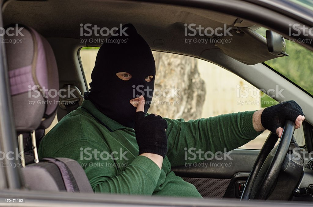 Masked robber puts his finger to lips stock photo