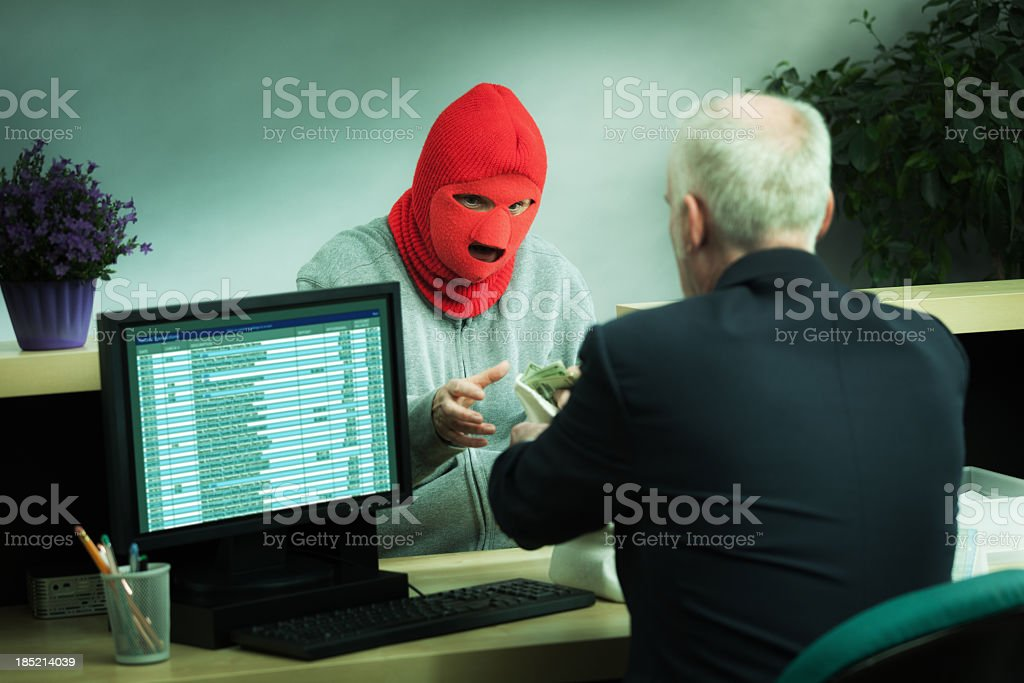 Masked Robber Robbing a Retail Bank Counter with Teller Hz stock photo