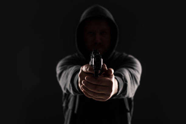 Masked robber with gun aiming into the camera against a black background stock photo