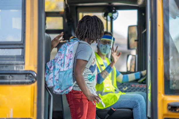 Masked school children getting off the bus stock photo