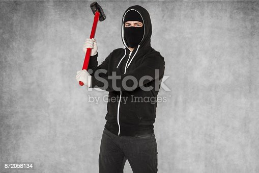istock A masked stranger takes an attack with large hammer 872058134