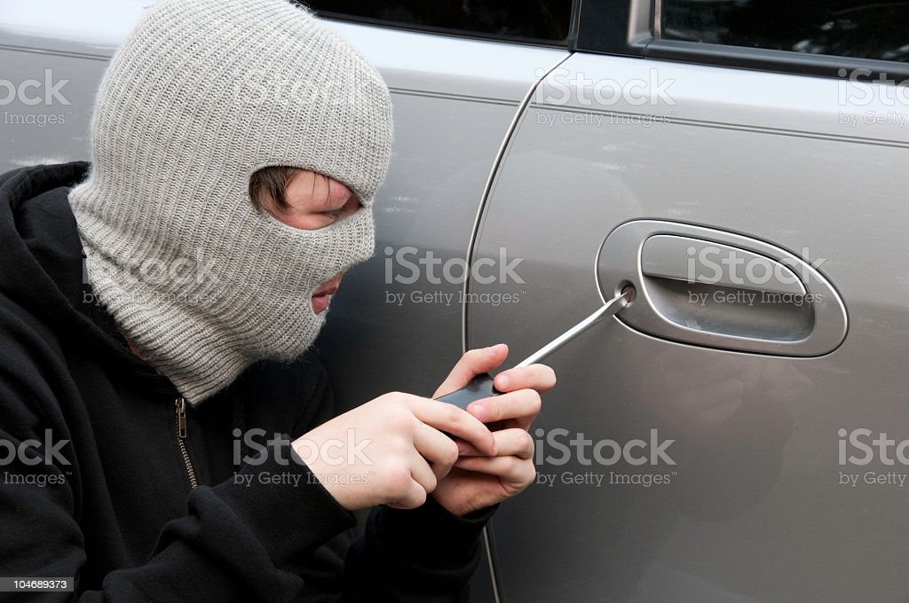 Masked Teenage Boy Breaking into a Car stock photo