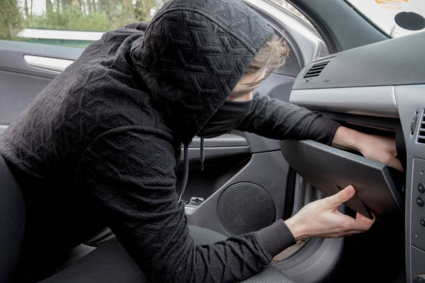 Masked teenage criminal stealing from a car stock photo