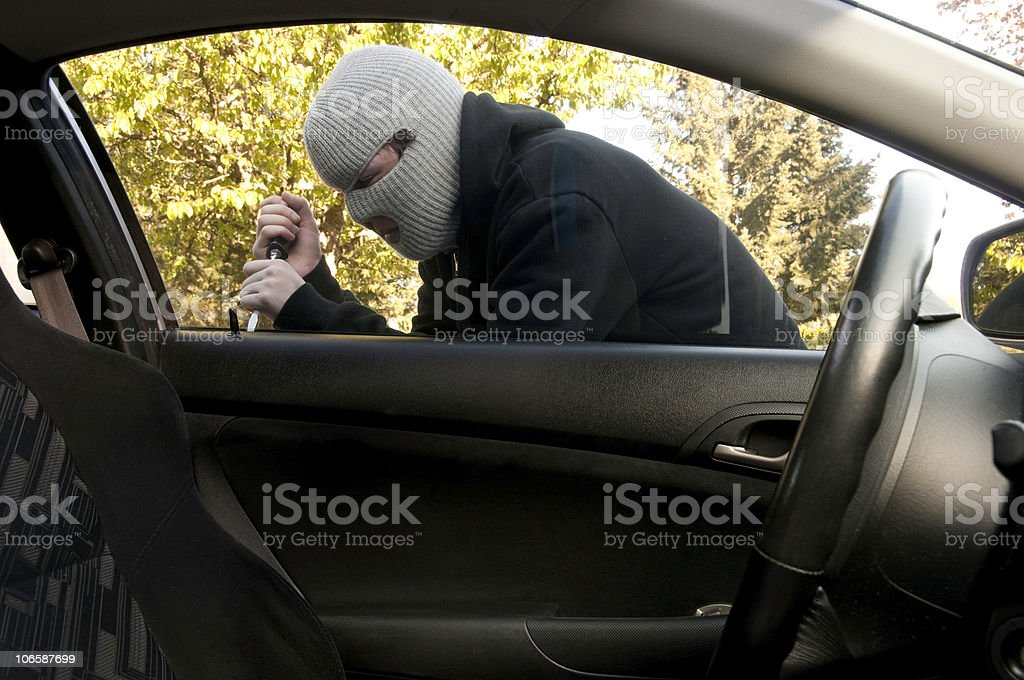 Masked Teenager Breaking into a Car stock photo
