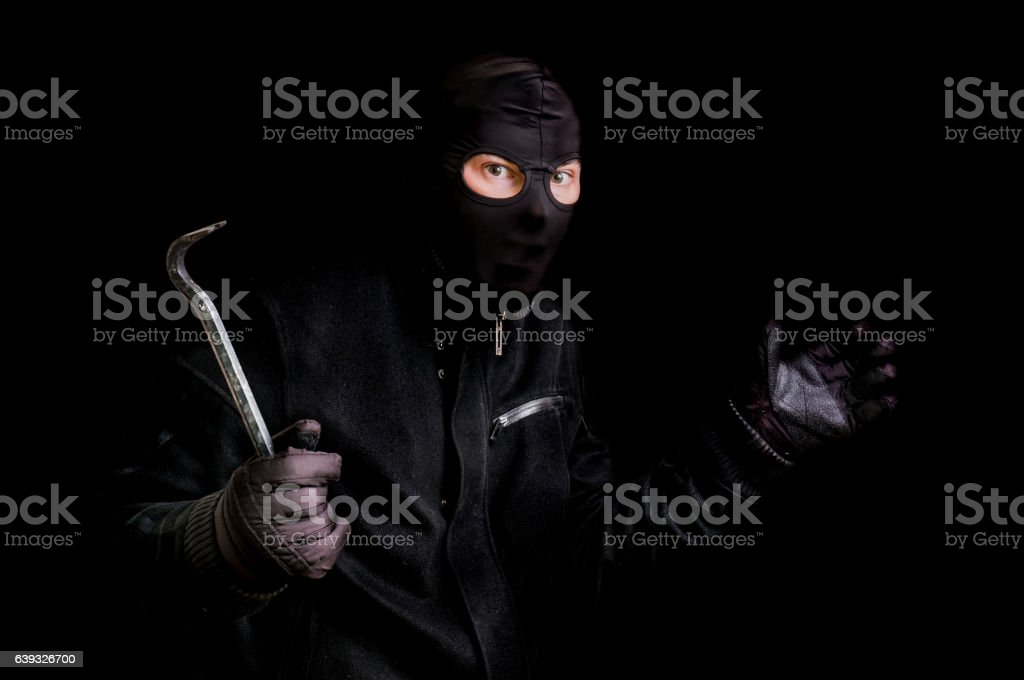 Masked thief in balaclava with crowbar isolated on black stock photo