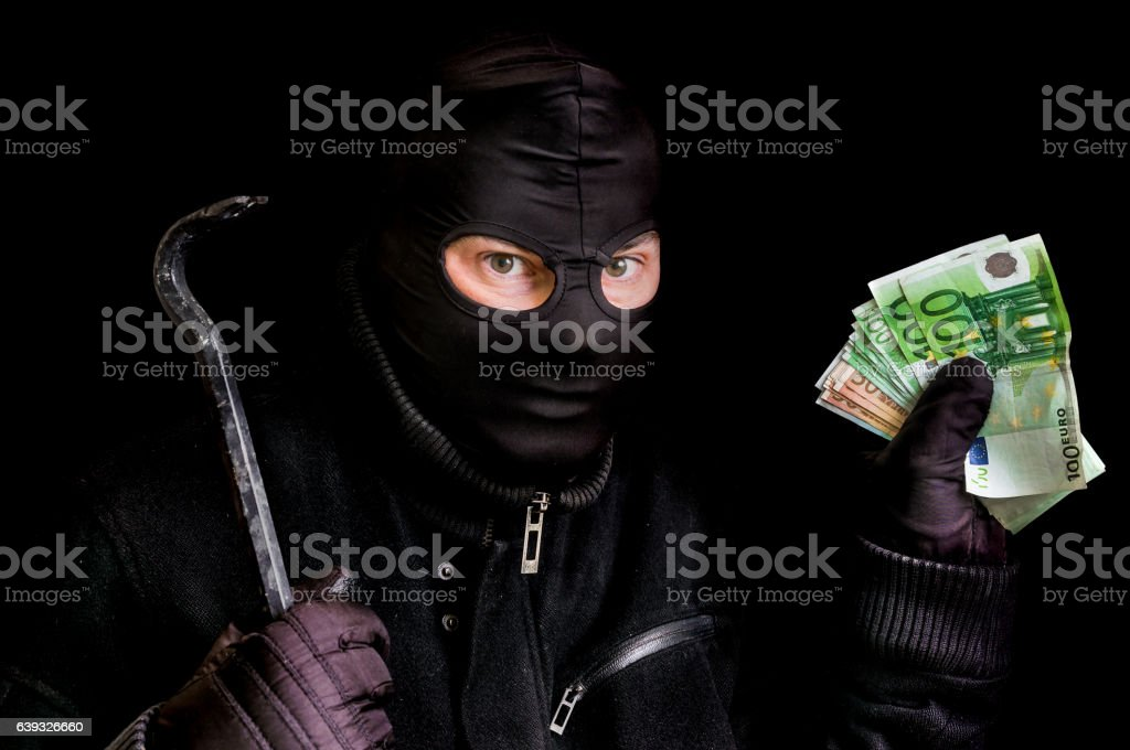Masked thief in balaclava with stolen money isolated on black stock photo