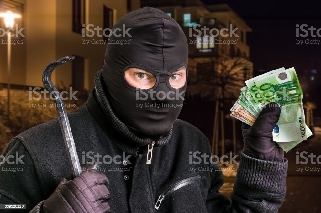 Masked thief in balaclava with stolen money stock photo