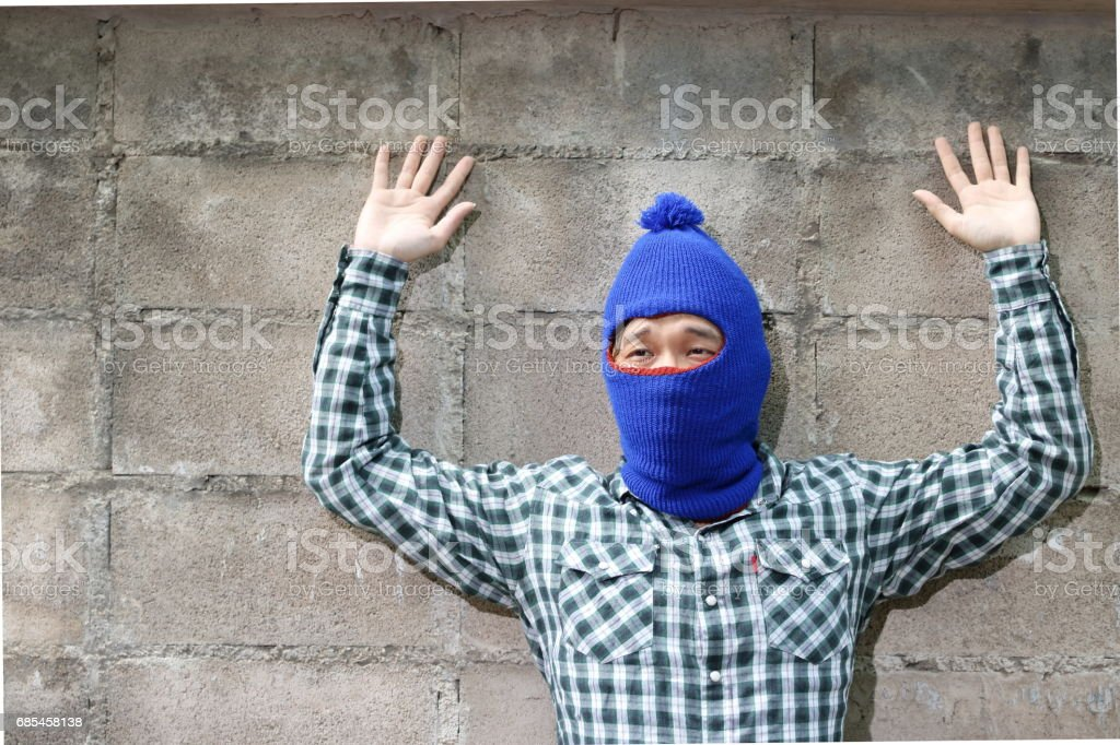 Masked thief raised arms with brick wall background. Catch burglar concept. foto de stock royalty-free