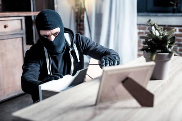 Ladrão mascarado roubando dinheiro da tabela - foto de acervo