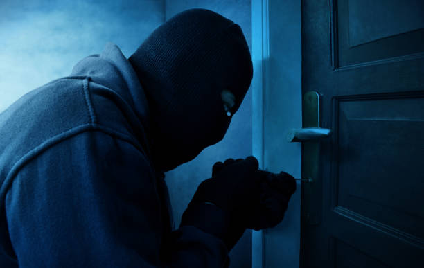 masked thief using lock picker to open locked door - thief stock photos and pictures