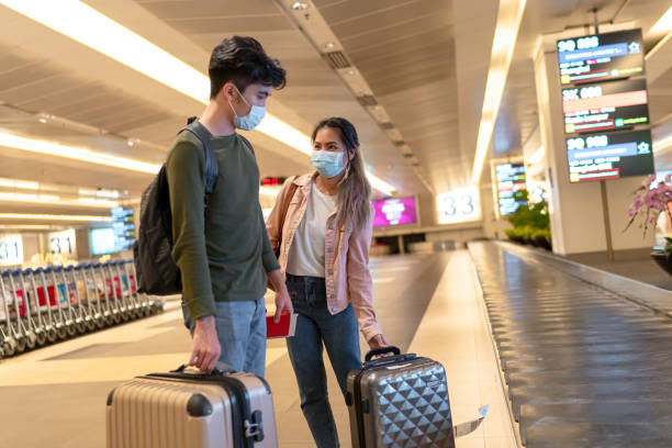 masked travelers at the airport - covid flight imagens e fotografias de stock