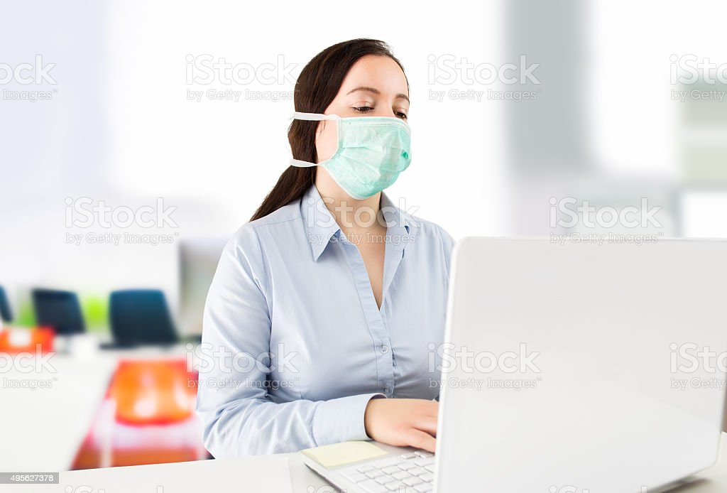 Masked woman in the office stock photo