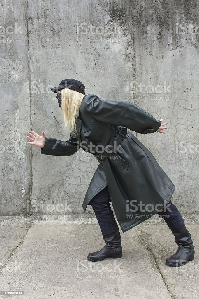 Masked woman runs to the wall royalty-free stock photo