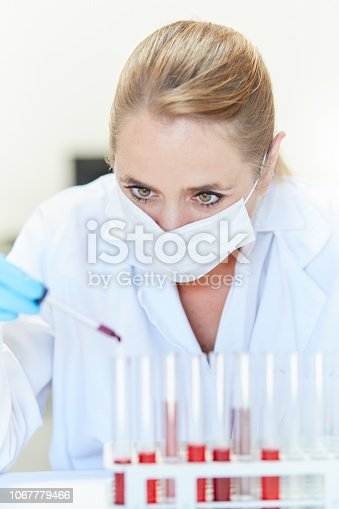 A beautiful female scientist wearing a protective mask holds a pipette and drips red liquid, possibly blood, into one of a series of test tubes,