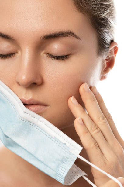 Maskne - acne breakouts from wearing a face mask stock photo