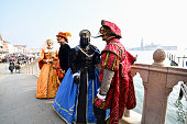Venice, Italy - February 18th, 2020. Venetian masks posing on St. Mark's Square during 2020 Carnival just before the cancellation.