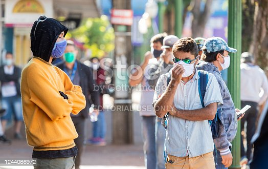 Mask-protected population awaits service outside bank branch to receive emergency benefit from the Brazilian government during coronavirus pandemic