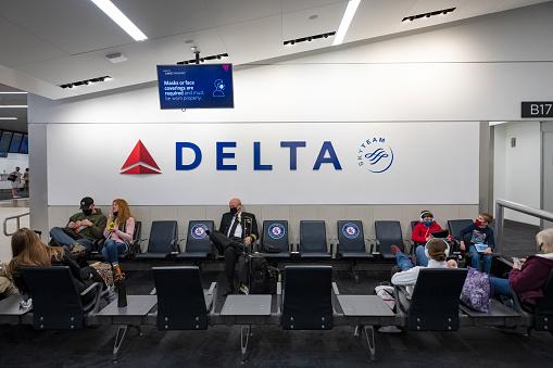 Atlanta, USA - January 23, 2021:  Passengers and a pilot wear face masks because of Covid-19 as they wait at a Delta Air Lines gate at Hartsfield-Jackson Atlanta International Airport.