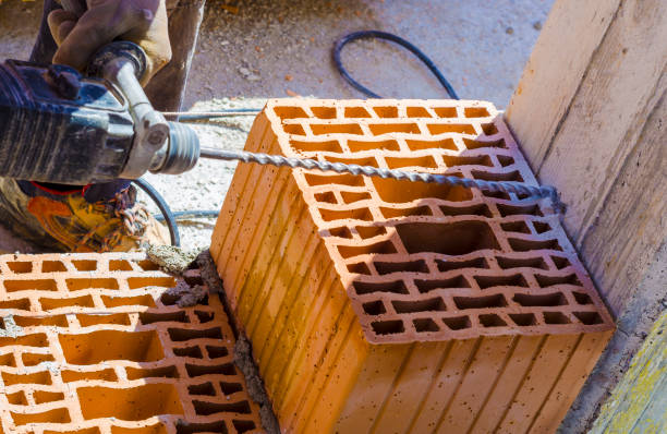 mason drills a hole with a power drill on a column in of reinforced concrete. selective focus on drill - pillar drill stock photos and pictures