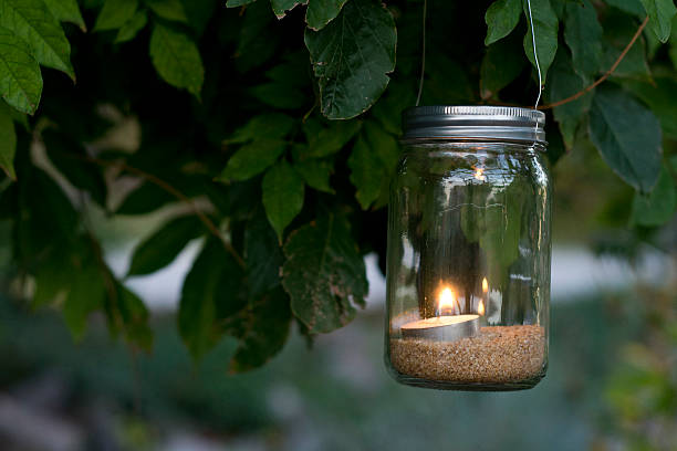 Mason jar candle hanging from tree stock photo