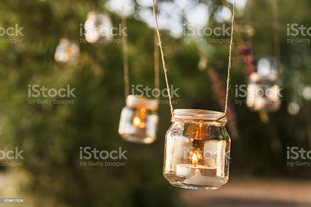 mason jar candle hanging on tree for wedding decor stock photo
