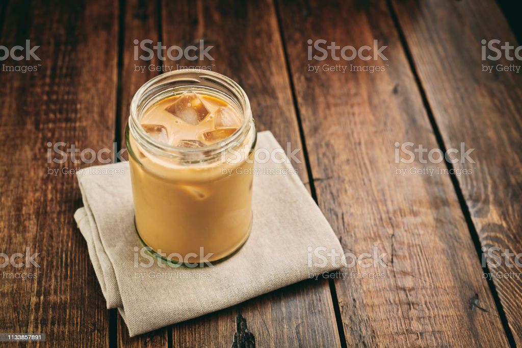 Mason Jar filled with iced coffee with double cream on a rustic table top. stock photo