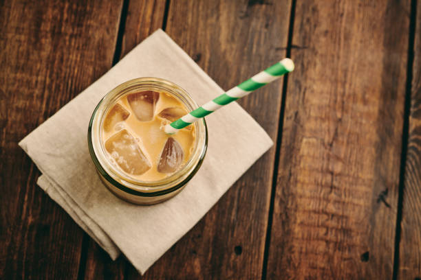 mason jar filled with iced coffee with double cream on a rustic table top. - iced coffee stock pictures, royalty-free photos & images