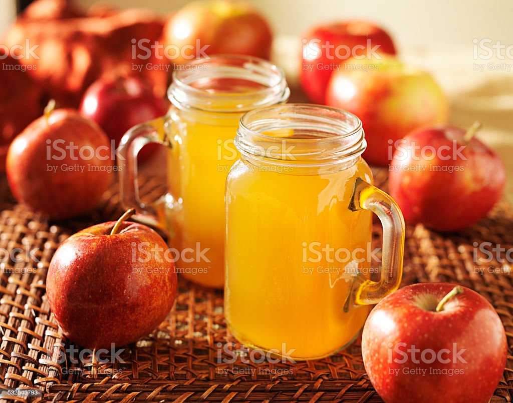 mason jars filled with hot apple cider stock photo