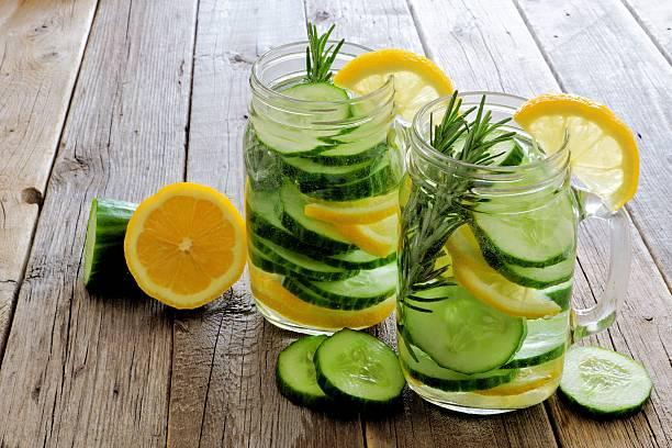 mason jars of detox water with lemon, cucumber on wood - gurke gesund stock-fotos und bilder
