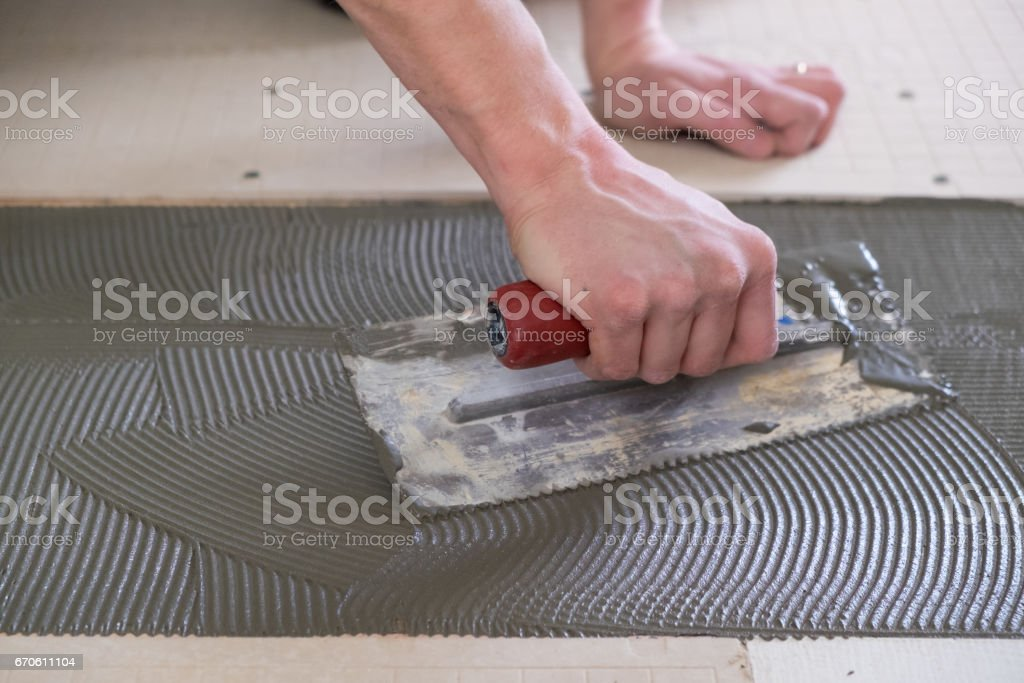 Mason Laying Down Thinset for Tile Project stock photo