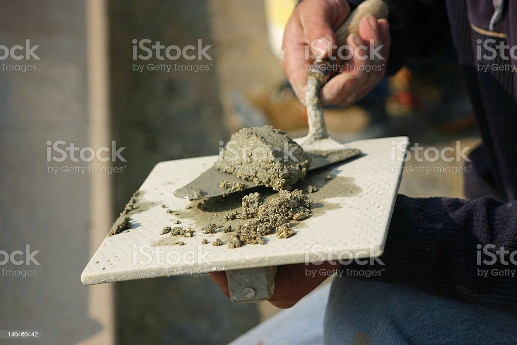 A mason using his trowel to spread grout  royalty-free stock photo
