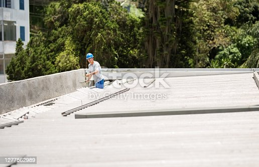 Shot of a mason worker wearing hardhat constructing a rooftop with concrete