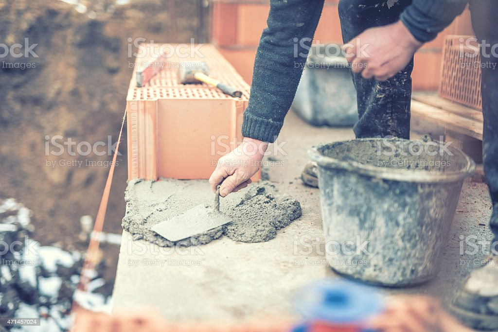 mason working with construction spatula and leveling mortar, creating walls stock photo