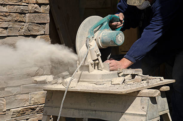 Masonry contractor using a  cutting saw stock photo