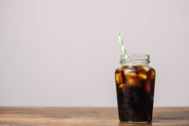 masonry jar filled with iced cold brew coffee. - iced coffee stock photos and pictures