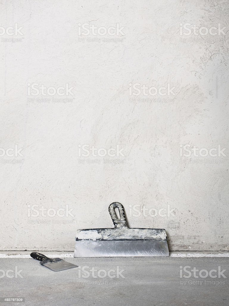 Masonry trowels near a grey plaster wall stock photo