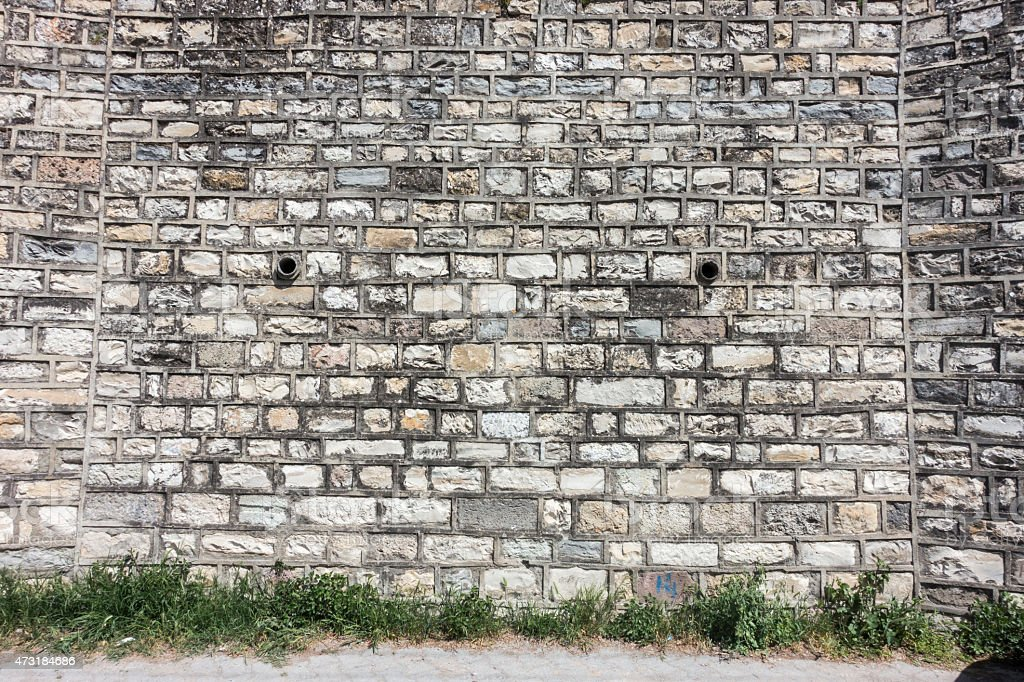 ancient stone wall with lines of brick