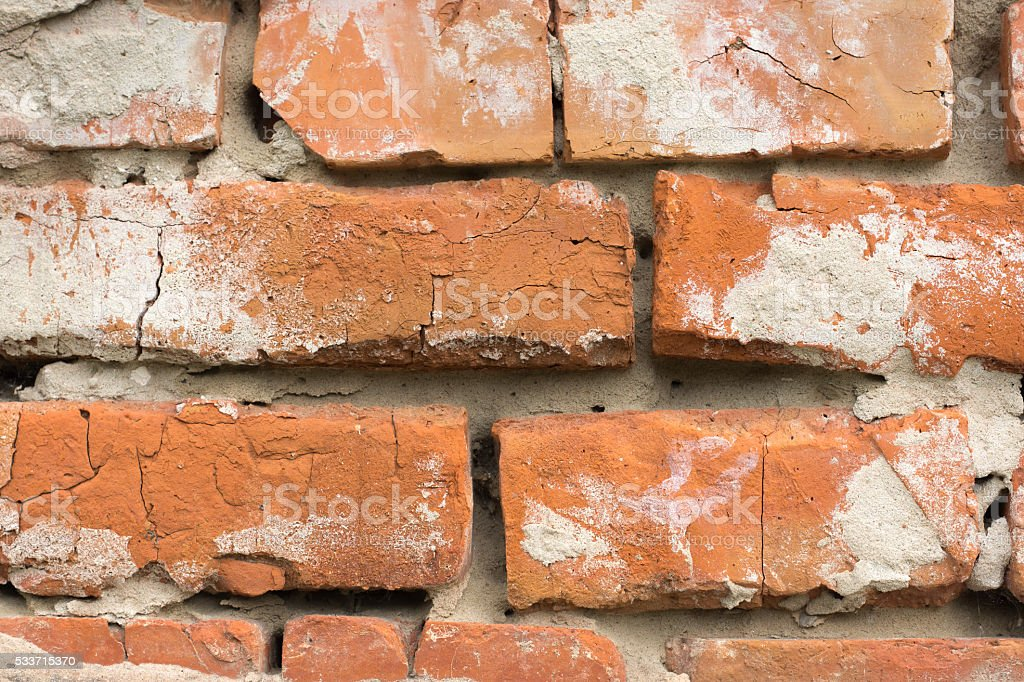 Masonry walls made of red bricks with traces of crumbling plaster