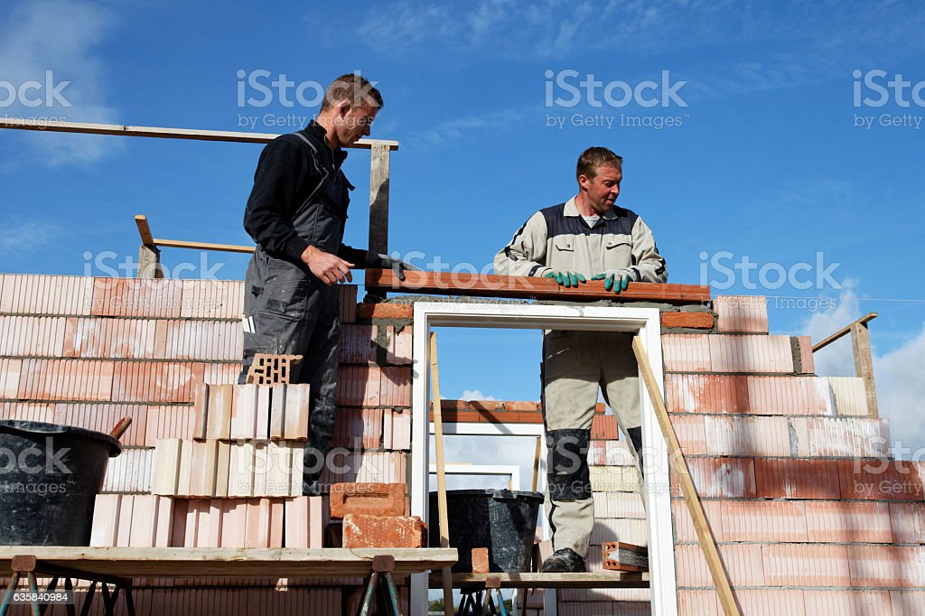 Masons bricklayers putting a lintel as a team together outdoors stock photo